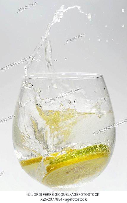Citrus fruits, lemon and lime slices splashing in a glass on white background