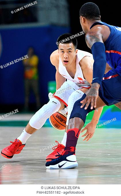 Zhao Jiwei (L) of China plays the ball during the Basketball Preliminary Round Group A match of the Rio 2016 Olympic Games at the Carioca Arena 1