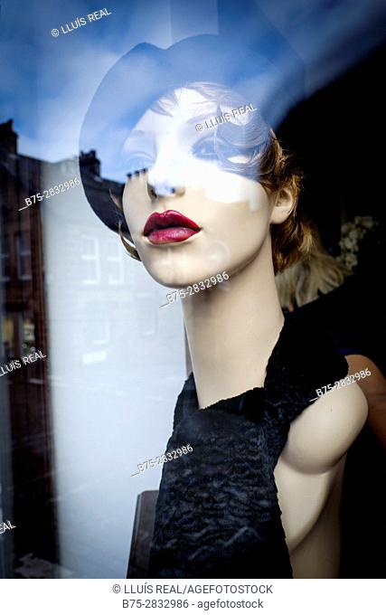 Female mannequin with beret in shop window, reflections on the glass. Harrogate, North Yorkshire, England, UK
