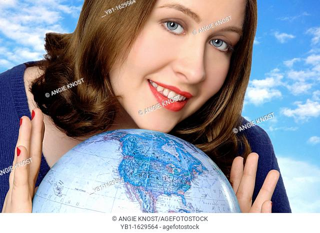 Attractive Caucasian woman holding a globe and smiling  Focus is on North American continent