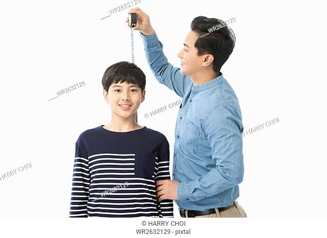 Smiling father measuring his adolescent son's height