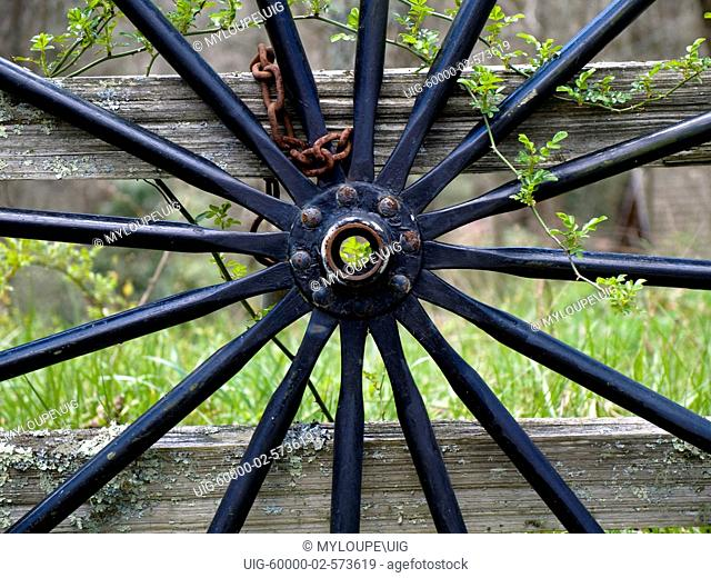 Old wooden spoked wagon wheel leaning against a split-rail fence