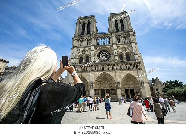Caucasian woman photographing building, Paris, Ile de France, France