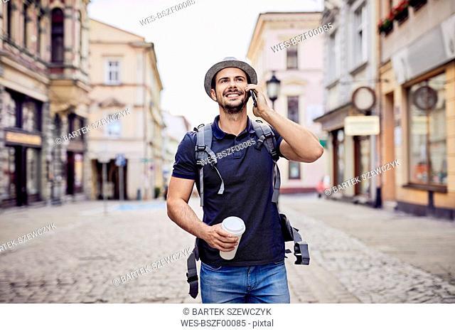 Traveler talking on the phone while walking down city street