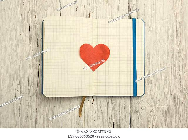 Blank notepad with red heart on wood background