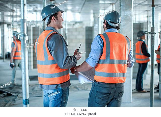 Rear view of site manager and builder meeting with blueprint on construction site