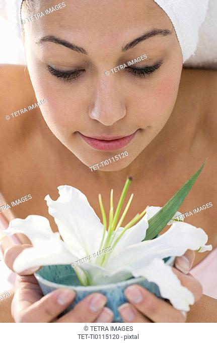 Woman with towel smelling flower