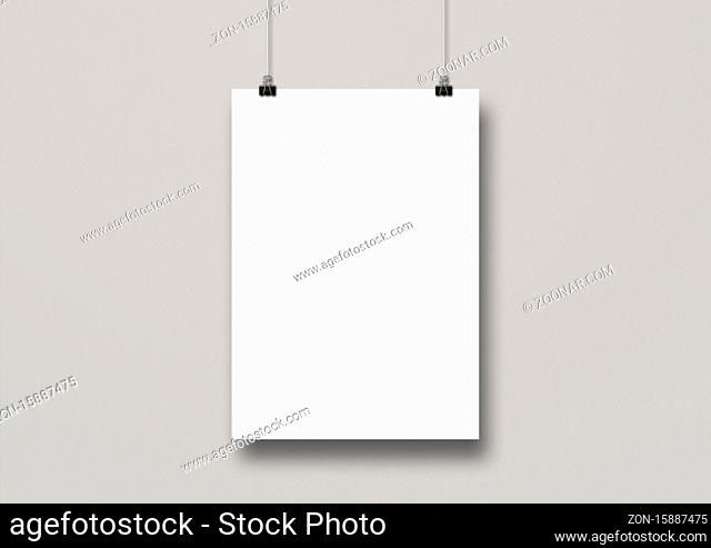 White poster hanging on a clean wall with clips. Blank mockup template
