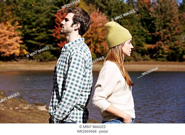 Two people, a couple back to back standing by a lake