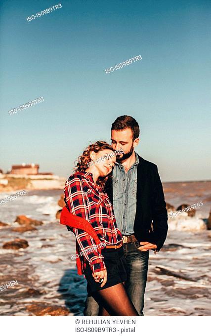 Romantic mid adult couple standing on beach, Odessa Oblast, Ukraine