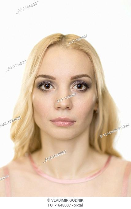 Portrait of beautiful woman with blond hair against white background