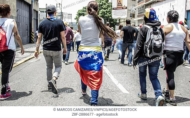 Demonstrators run from tear gas and charging police officers during anti-government protests in Caracas, Venezuela, Wednesday, April 19, 2017