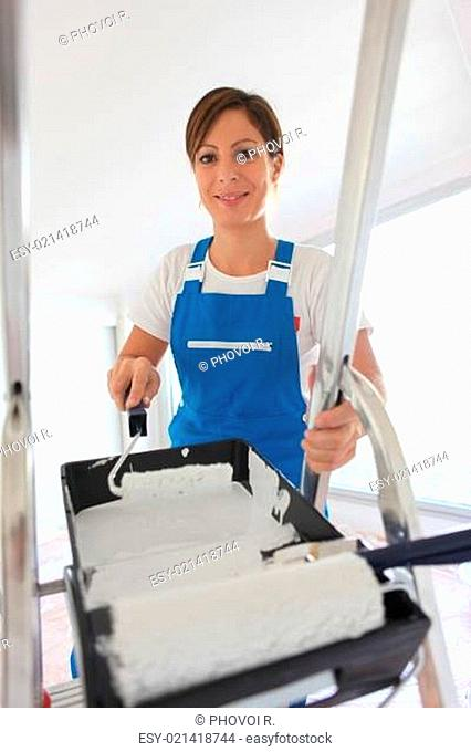 Female decorator climbing ladder