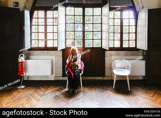Woman listens to audio tour device at a photo exhibition in the Casa dei Tre Oci, in Guidecca, in Venice, Italy