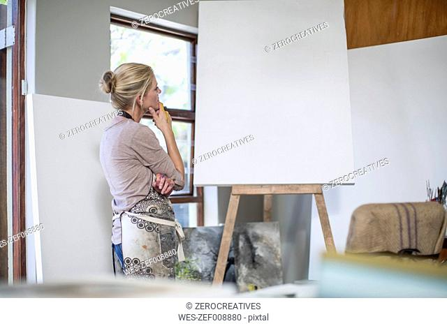 Woman observing canvas before setting up artwork at home studio