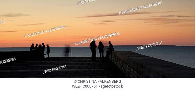 Estonia, Tallinn, Harbour, people on pier, afterglow
