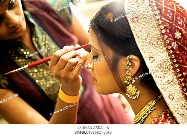 Indian woman in traditional clothing having make up applied