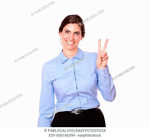 A portrait of a gorgeous latin woman with victory sign standing and smiling at you on isolated studio