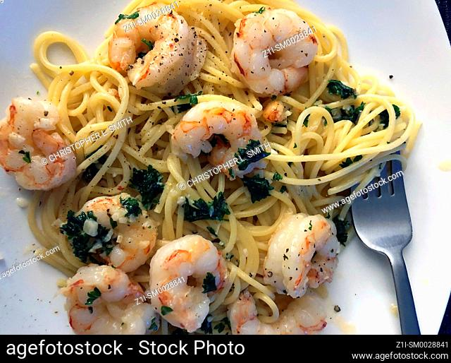 Garlic butter grilled Shrimp and spaghetti with herbs on a white plate