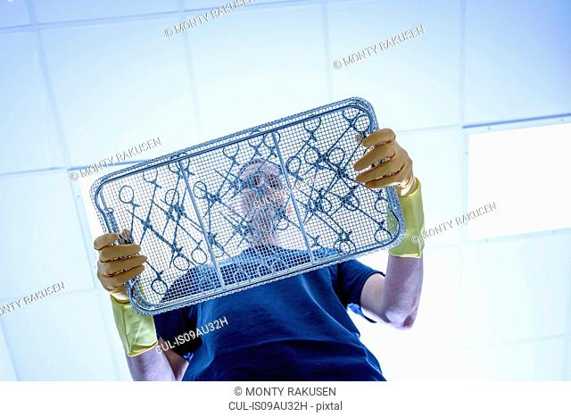 Worker with tray of surgical instruments in surgical instrument factory, low angle view