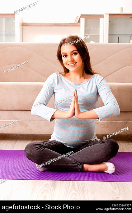 Young pregnant woman doing sport exercises at home