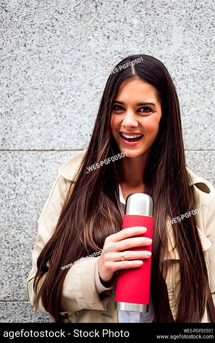 Beautiful woman holding bottle in front of wall