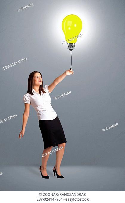 Pretty lady holding a light bulb balloon