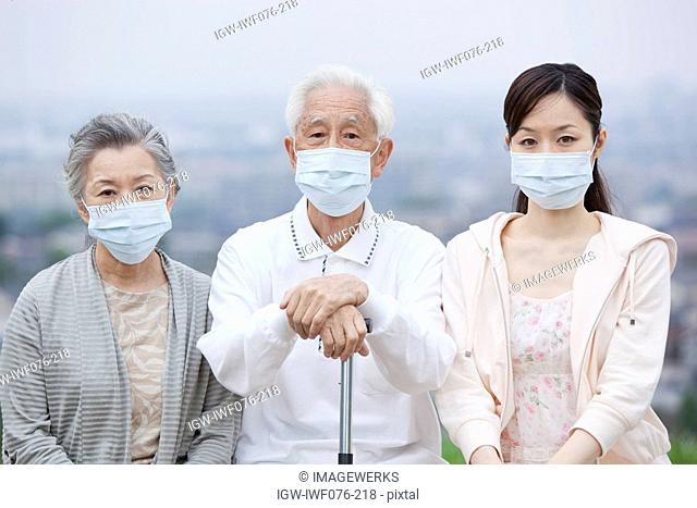 Japan, Tokyo Prefecture, Parents with daughter wearing flu mask, portrait