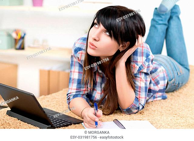 Teenager girl studying at home lying on sofa