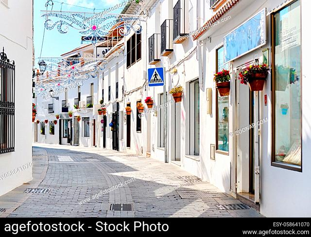 Mijas white washed street, small famous village in Spain. Charming empty narrow streets with New Year decorations, on houses walls hanging flower pots
