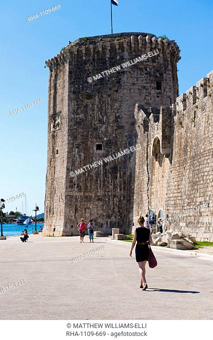 Tourist walking towards Kamerlengo Fortress (Gradina Kamerlengo), Trogir, UNESCO World Heritage Site, Dalmatian Coast, Croatia, Europe