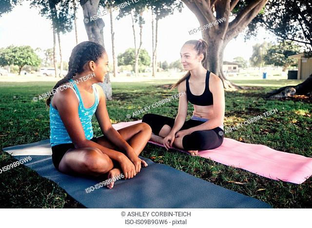 Two schoolgirls chatting on yoga mats on school sports field