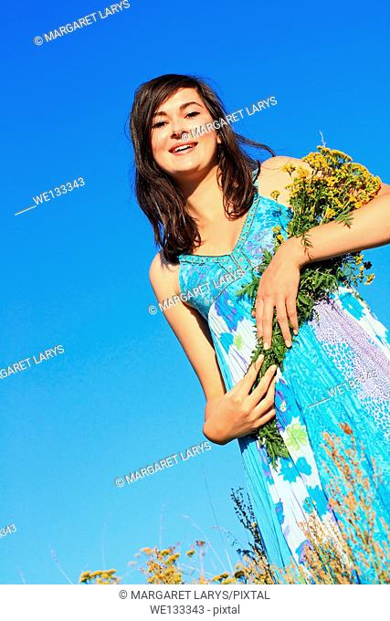 Young, beautiful girl in a blue dress holding wildflowers and looking up with a smile