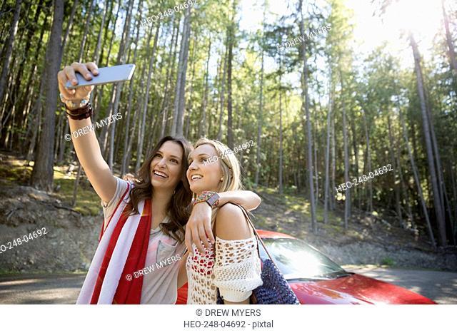 Young women taking selfie outside car in woods