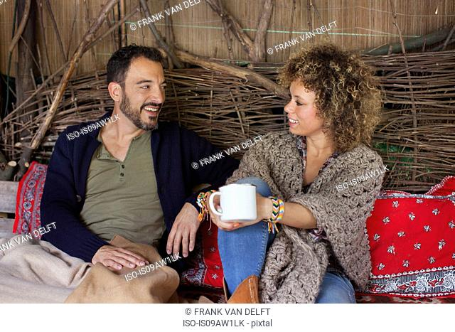 Couple chatting and drinking coffee in cabin