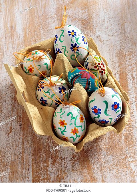 Painted eggs in an egg carton