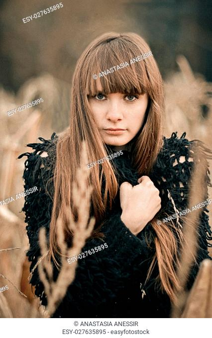 Shot in war, colors of beautiful girl with long hair and cute face hugging herself