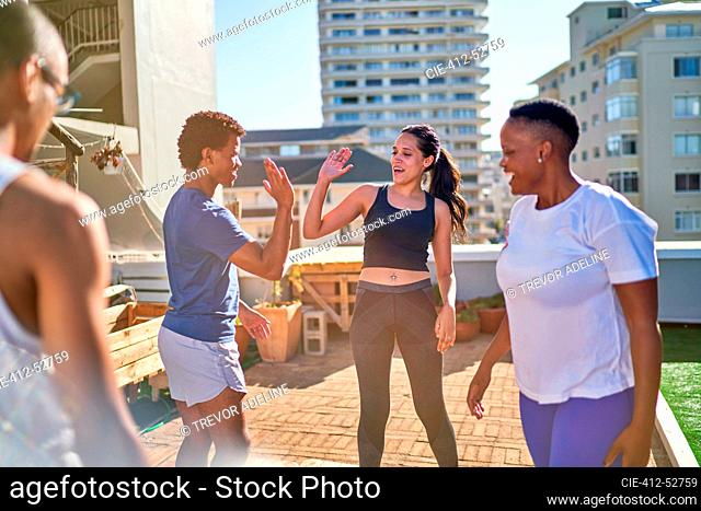 Young friends exercising and high fiving on sunny urban rooftop