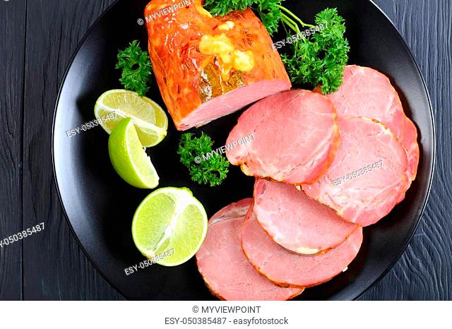 close-up of delicious ham cut in slices served with parsley and fresh citrus wedges on black plate on black wooden table, view from above, macro