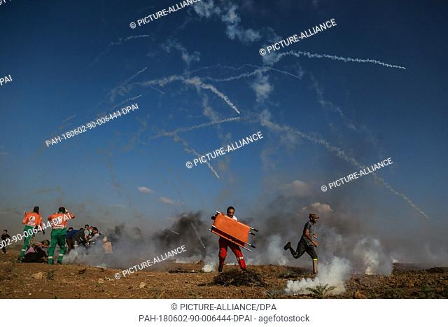 Israeli tear gas canisters falls towards Palestinian protesters and medics during clashes with Israeli security forces along the Israel-Gaza border