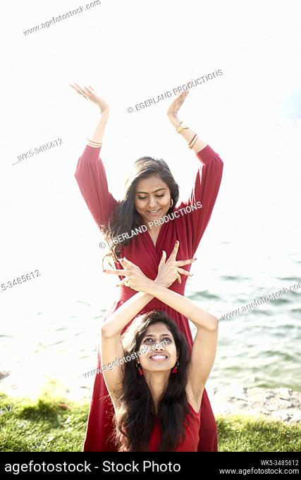 Two Indian women feeling energy of life, traditional Indian dance, old and young, by the lake. Tegernsee, Bavaria, Germany