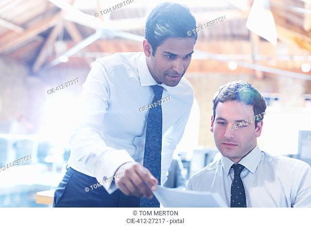 Businessmen reading paperwork in office