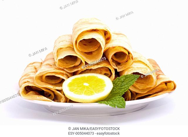 Delicious rolled crepes with lemon and mint, isolated on white background