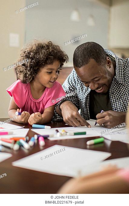 Father and daughter drawing in kitchen
