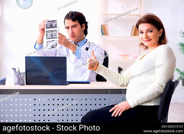Old pregnant woman visiting young male doctor