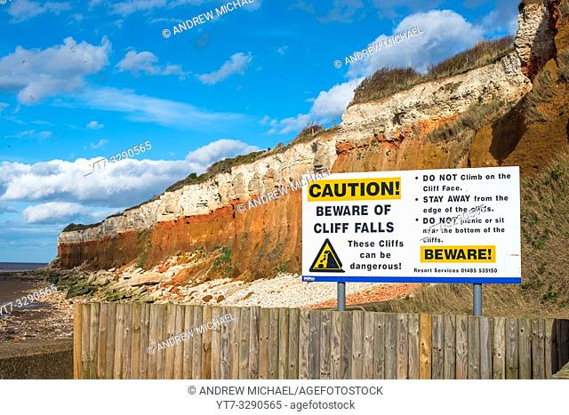 Signpost warning of coastal erosion at Hunstanton cliffs, North North coast, England, UK