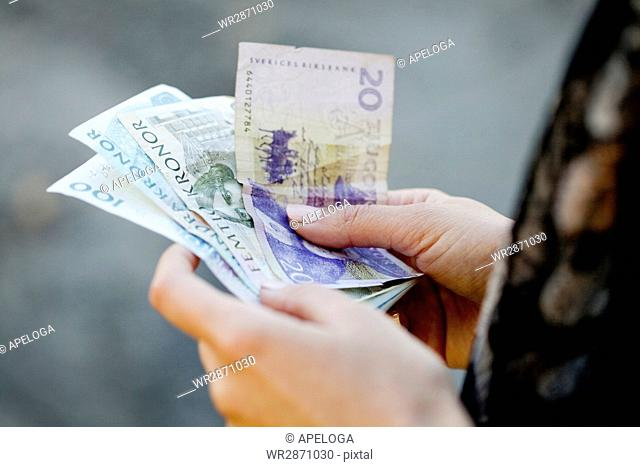 Cropped image of woman holding Danish banknotes