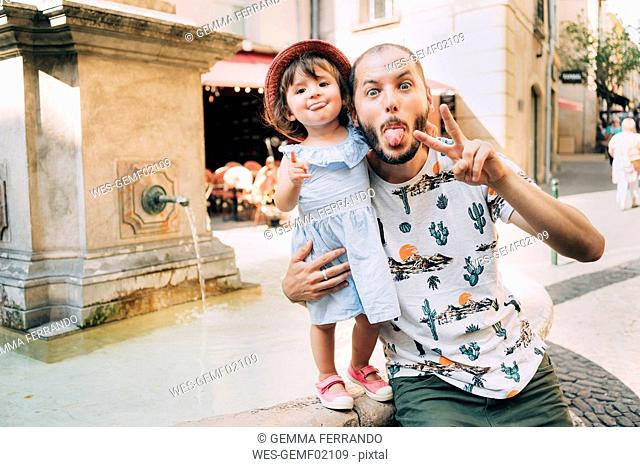 France, Aix-en-Provence, funny toddler girl and father with tongue out next to a fountain in the city