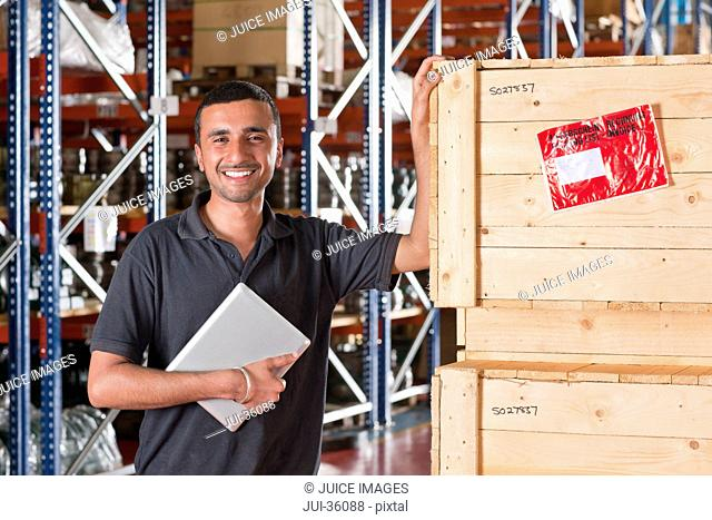Portrait of smiling worker holding digital tablet and leaning on crates in warehouse