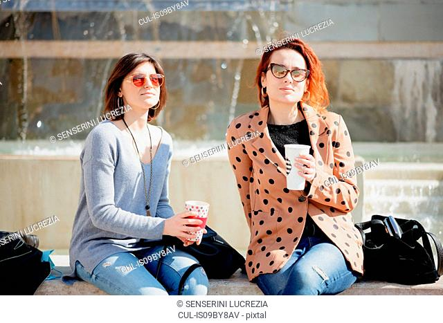Girlfriends taking coffee break in front of fountain, Arezzo, Toscana, Italy